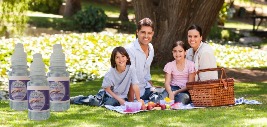 A family sitting at a picnic with Hand Sanitiser to the left.